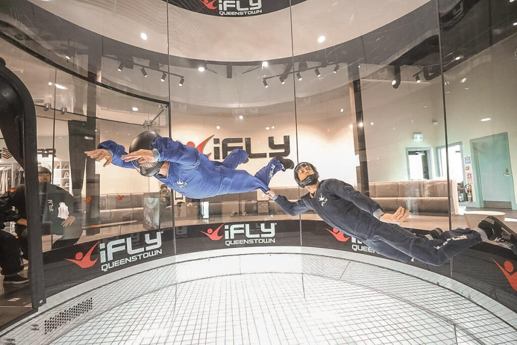 A customer and coach fly in the iFly wind tunnel