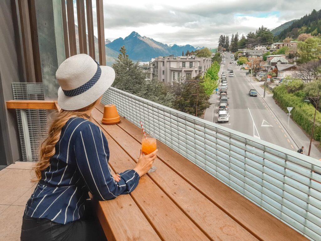 A lady leans on a bar on the balcony of the Miss Lucy's Restaurant in Queenstown, New Zealand