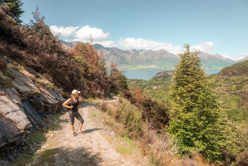 A lady stands on the trail of Mt Crichton Loop looking back at Lake Wakatipu