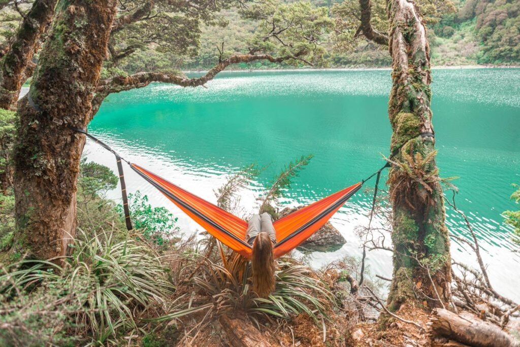 A lady sits in a hammock at Lake Mackenzie on the Routeburn Track