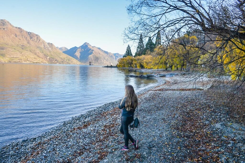 A lady looks out over Lake Wakatipu from the esplanade in Queenstown