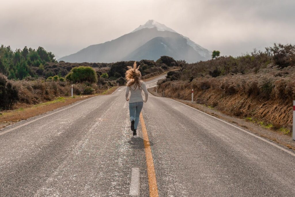 A lady runs on the road on Glenorchy-Queenstown Road