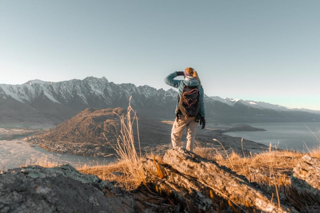 a lady looks at the remarkables Mountain Range from Queenstown Hill at sunrise