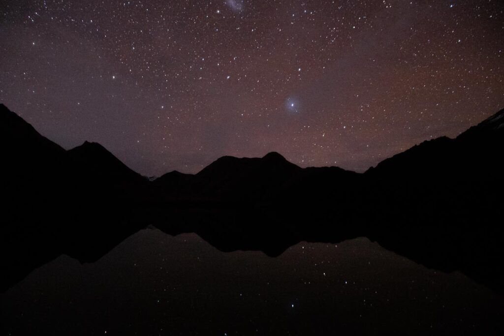 Moke Lake at night with reflections and the stars