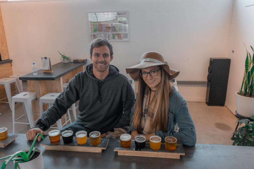 A couple sit at the Search Light Brewery with a flight of beers to try in Queenstown, New Zealand