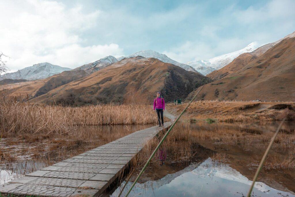 A lady walks across the small wooden bridge at Moke Lake to start the Moke Lake Loop