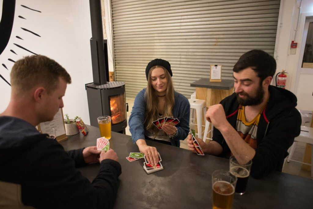A group of poeple play cards at the Searchlight Brewery in Queenstown
