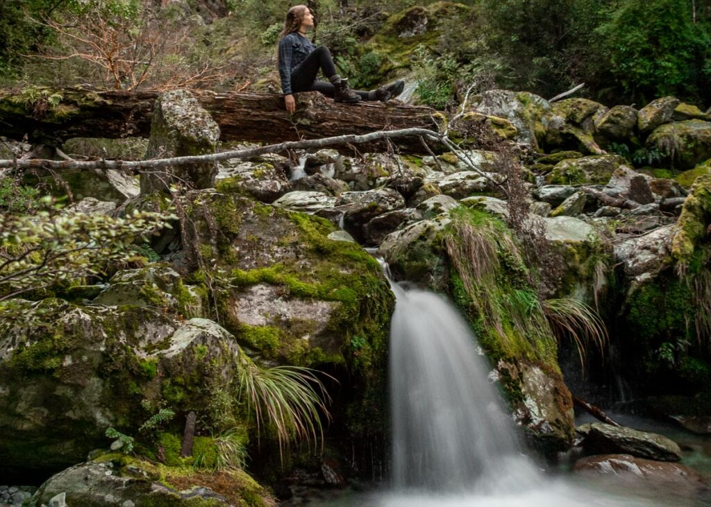A lady sits on a log on the upper section of Bridal Veil Falls on the Routeburn Track