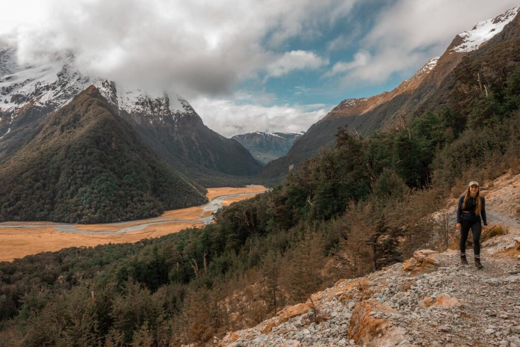 A lady hikes on a path on the Routeburn Track with the mountains in the background