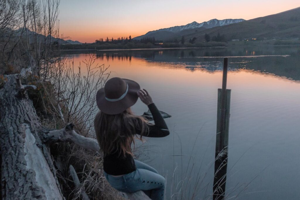 Sitting on a log on the shore of Lake hayes at sunset near Queenstown
