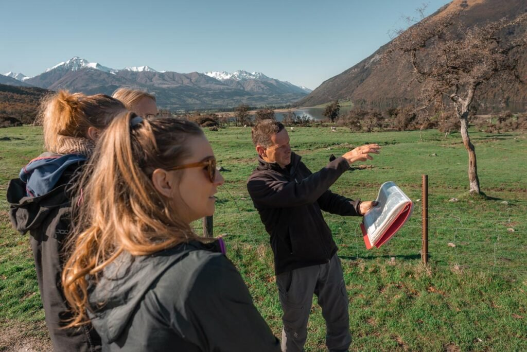 A group of people are shown a Lord of the Rings location by their guide on a tour in Glenorchy