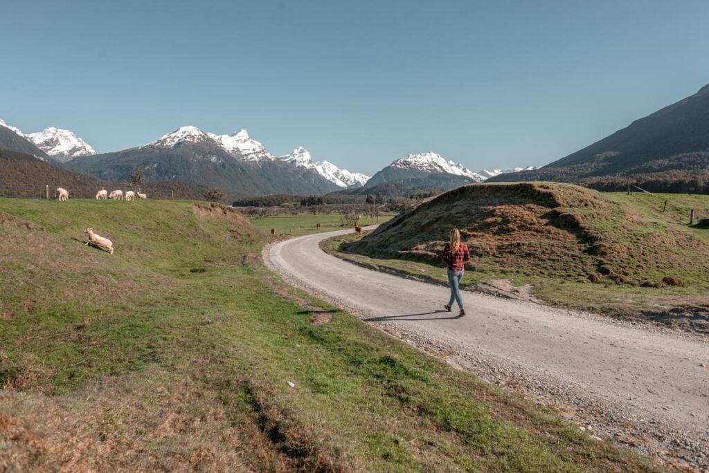 A lady walks along Glenorchy-Paradise Road near where Isengard in LOTR was filmed