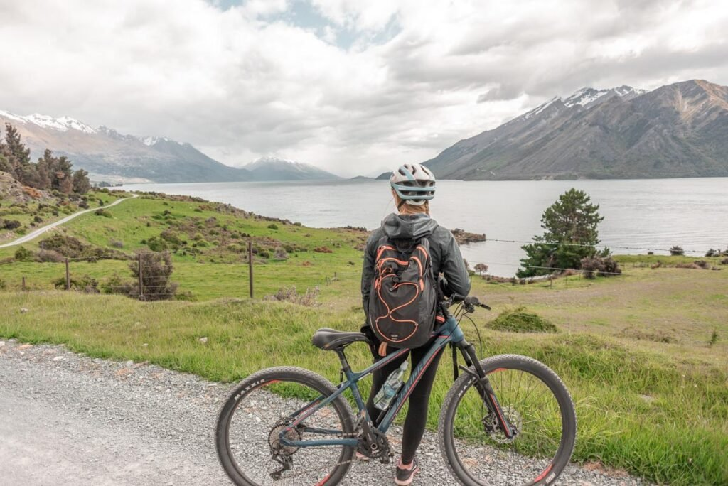 A lady poses with her mountain bike on the station to station ride just outside of Queenstown, New Zealand