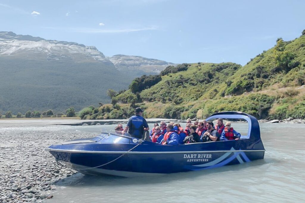 A jet boat from Dart River Jets sits on the beach with a group of tourists in it