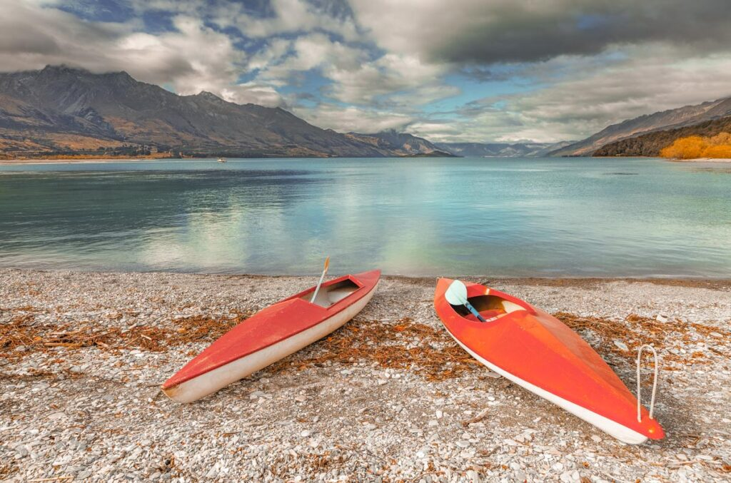 Two kayaks sit on the beach at Kinloch Campsite in Glenorchy