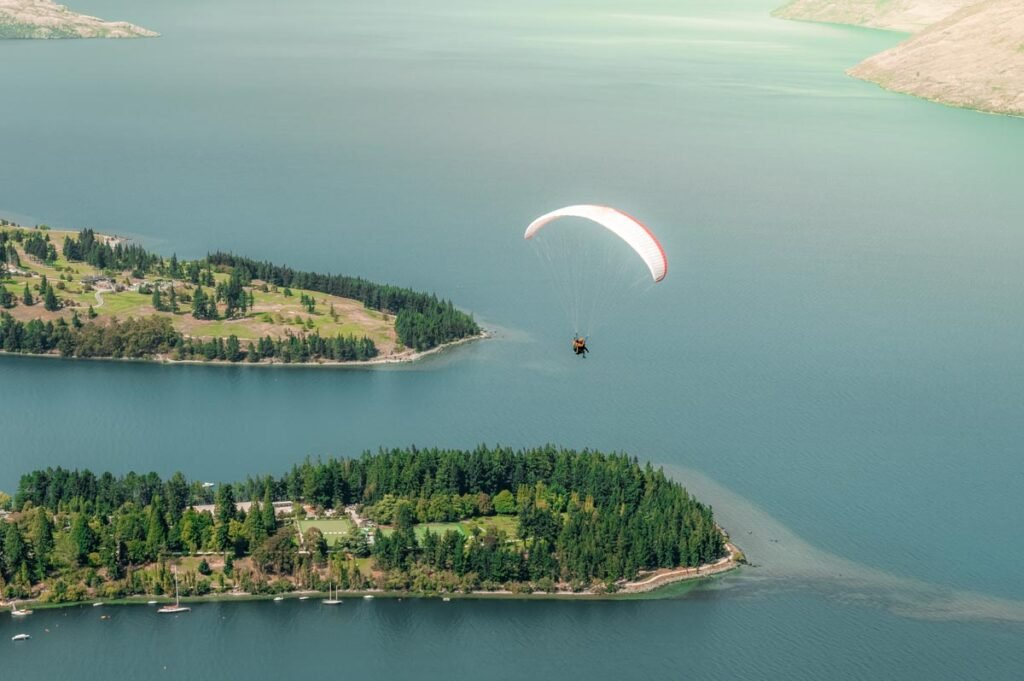 A person paraglides over Lake Wakatipu in Queenstown