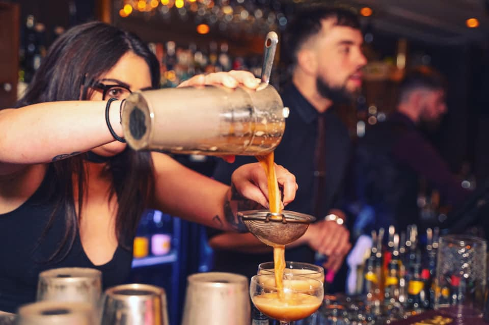 A bar tender pours a cocktail at The Bunker bar in Queenstown