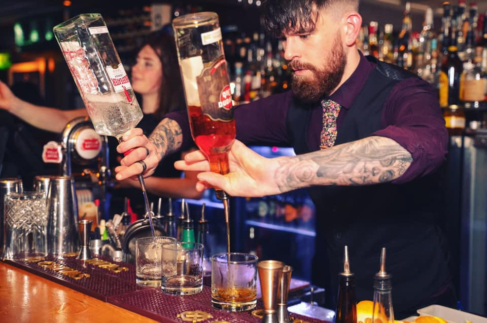 A bartender at Bunker Queenstown pours drinks at the bar
