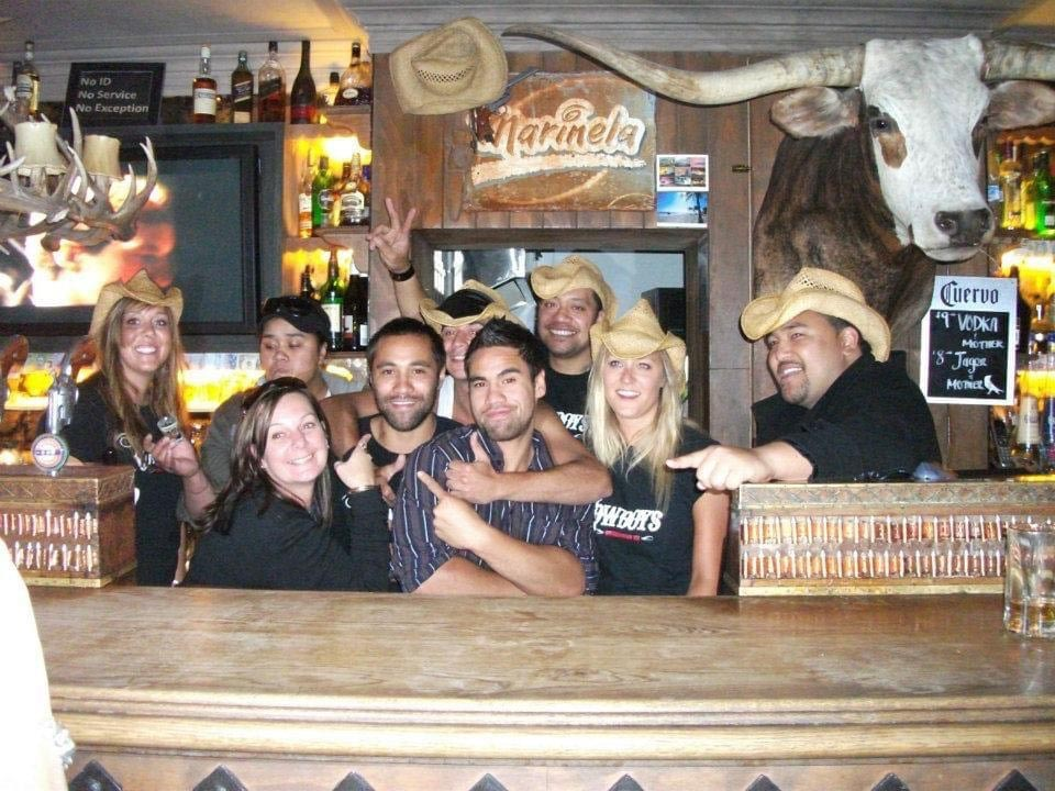 A group of people pose for a photo at Cowboys in Queenstown