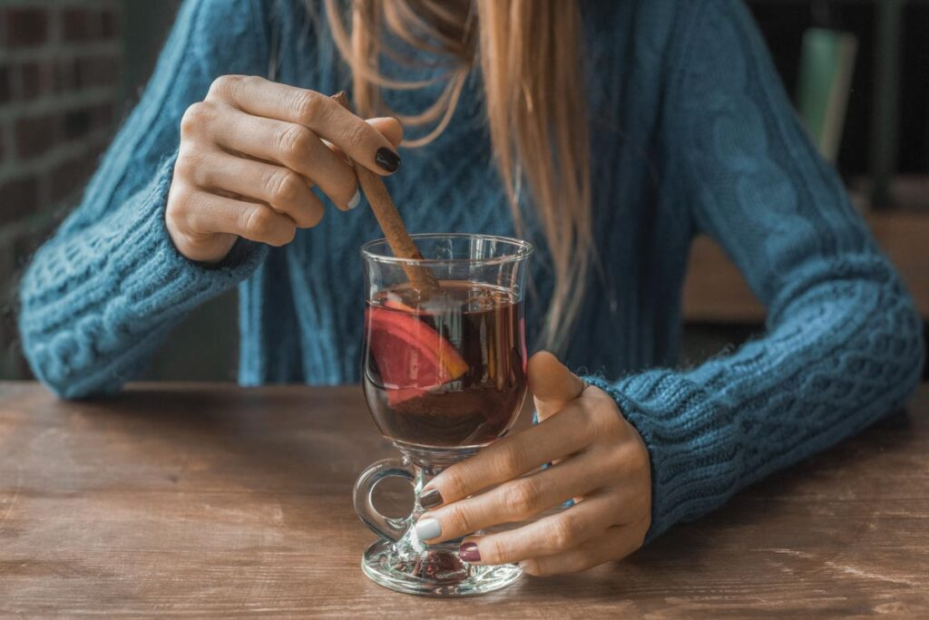 A lady drinks mulled wine at a table