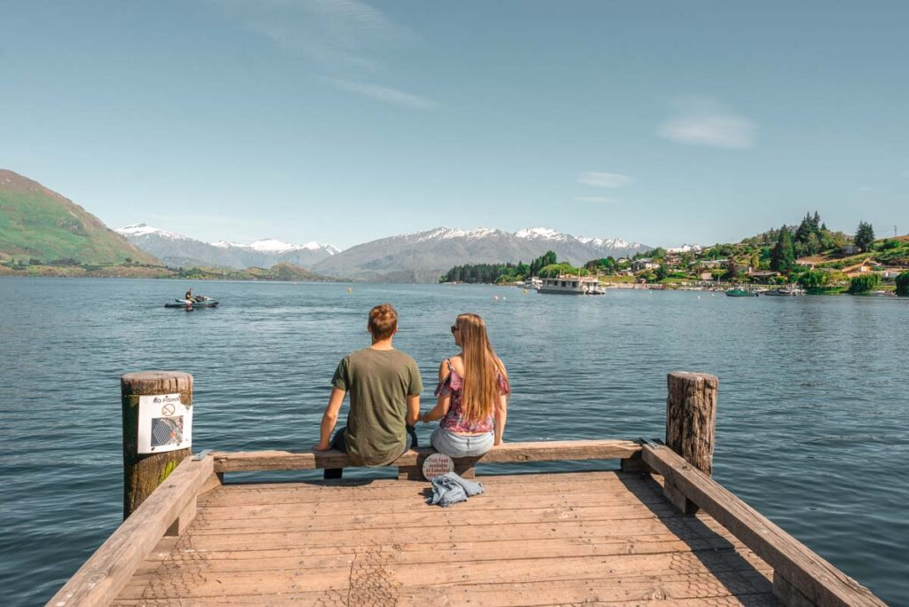 A couple sit on the Wanaka Jetty on a summers day