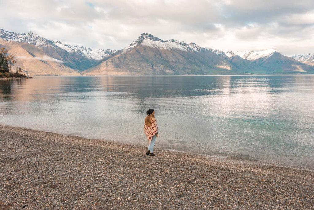 A lady walks the shoreline at Wilsons Bay, Queenstown-Glenorchy highway