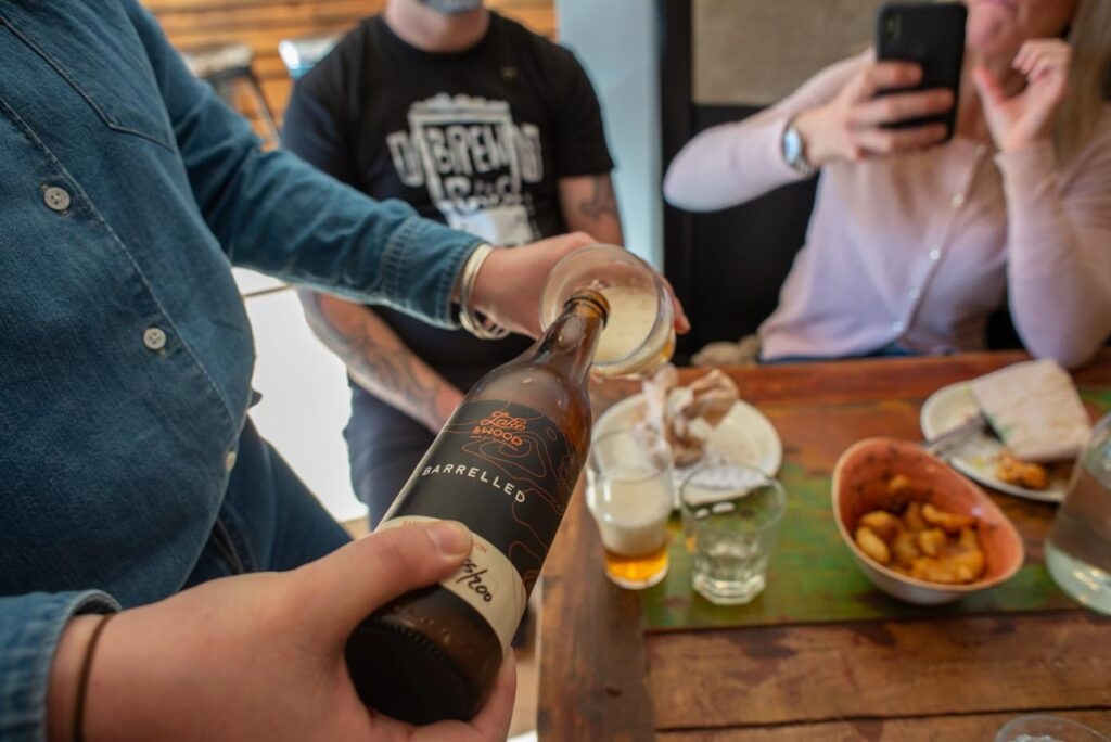 Pouring a bottle of Lake and Wood Beer Co at Slow Cuts in Arrowtown