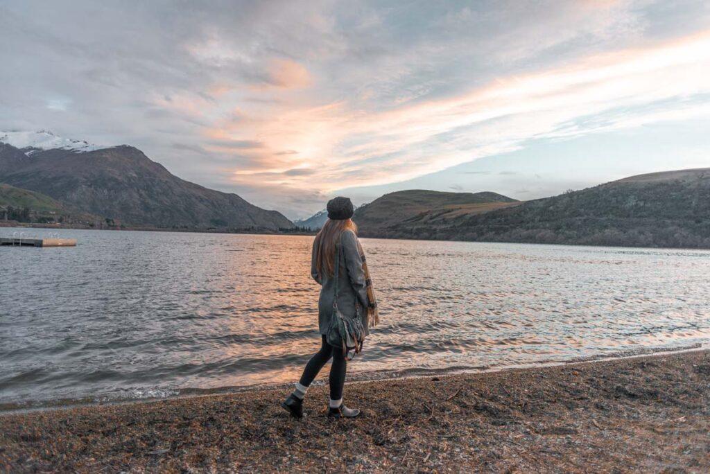 Bailey walks along Lake Hayes at sunset