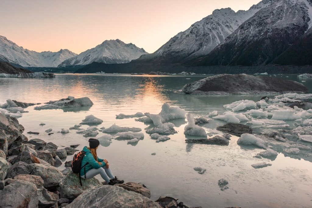 A lady sits ona  rock and watches the sunrise at Tasman River Viewpoint in Mount Cook National Park
