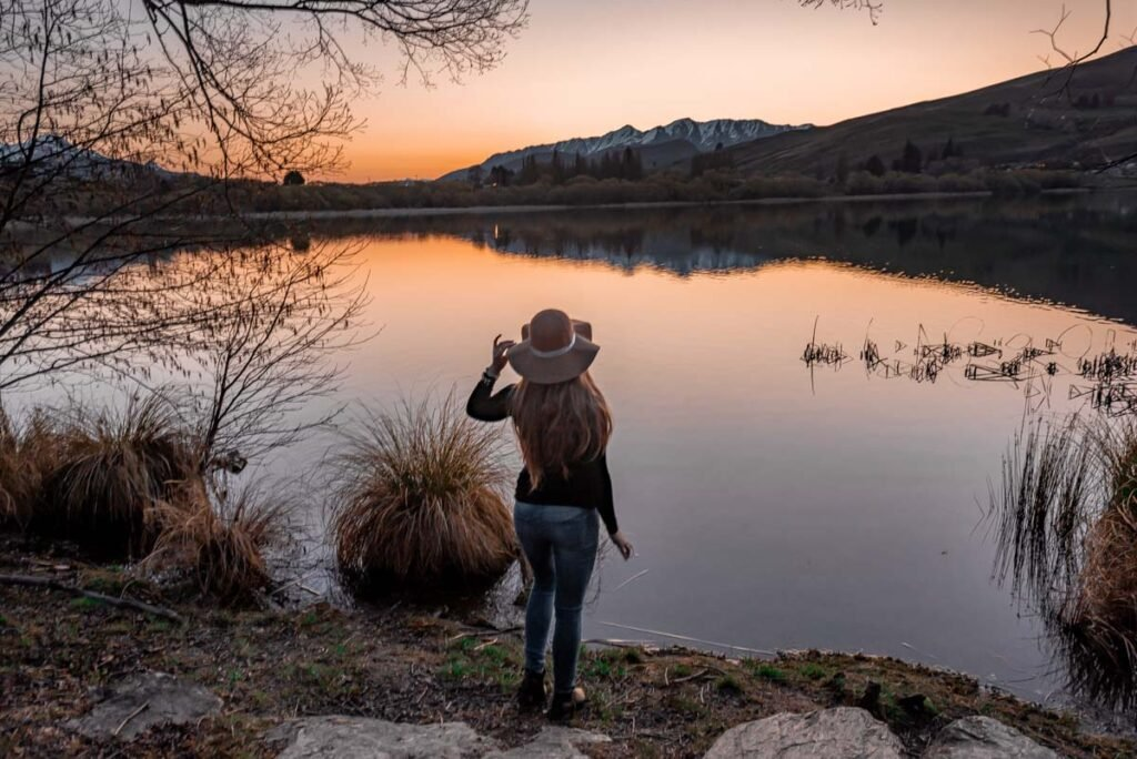 A lady stands on the hsores of Lake Hayes and admires the view at sunset