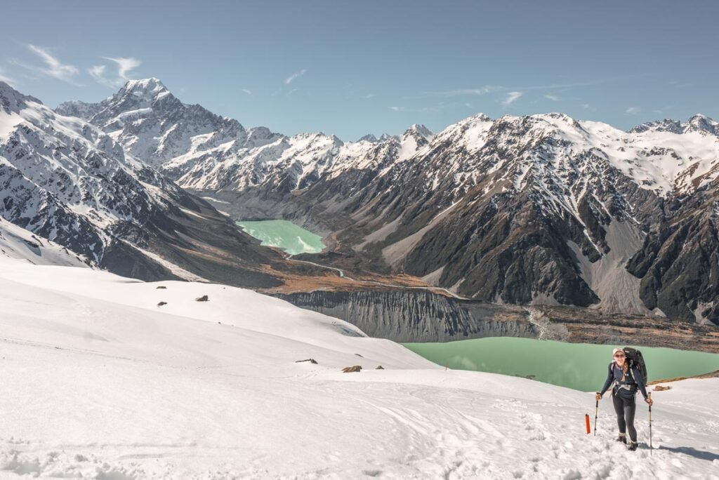 A lady hikes up to the Mueller Hut with views of Hooker Lake and Mount Cook in the background