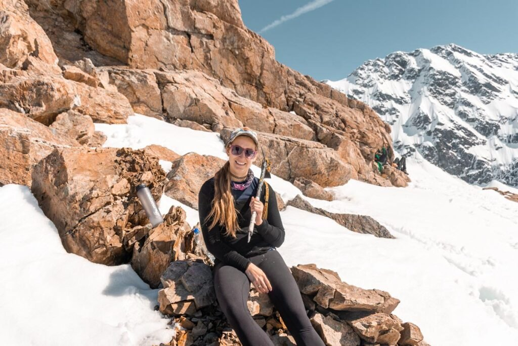 Bailey from My Queenstown Diary sits on a rock on her way to the Mueller Hut and smiles at the camera