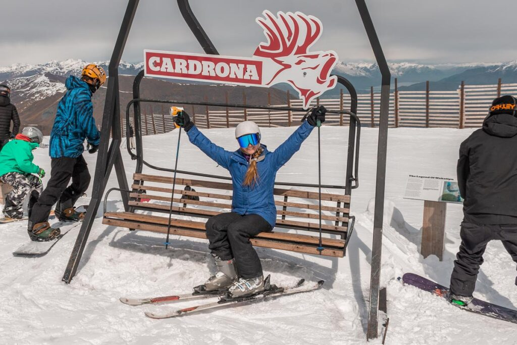 A lady sits on a seat at the top of Cardrona Ski Field