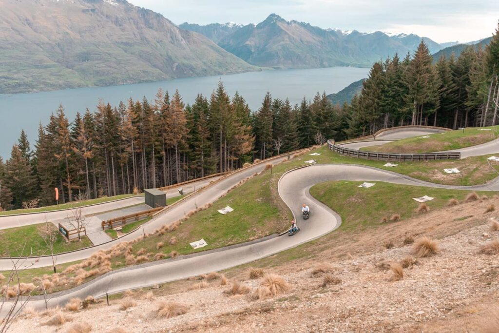 People ride the luge in Queenstown with views of Lake Wakatipu in the background