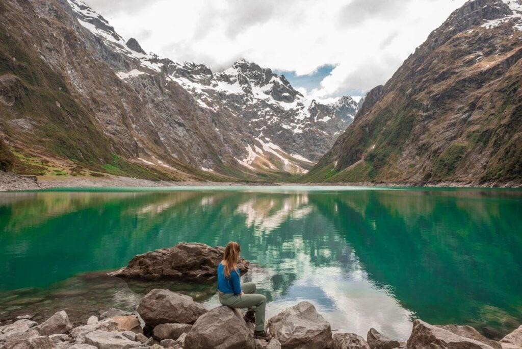 a lady sits on a rock at Lake Marian