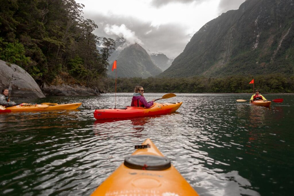 A lady Kayaks in Milford Sound while it's raining on a day trip from Queenstown