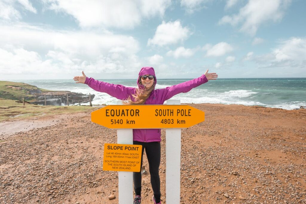 Bailey poses for a photo with the sign at Slop Point!