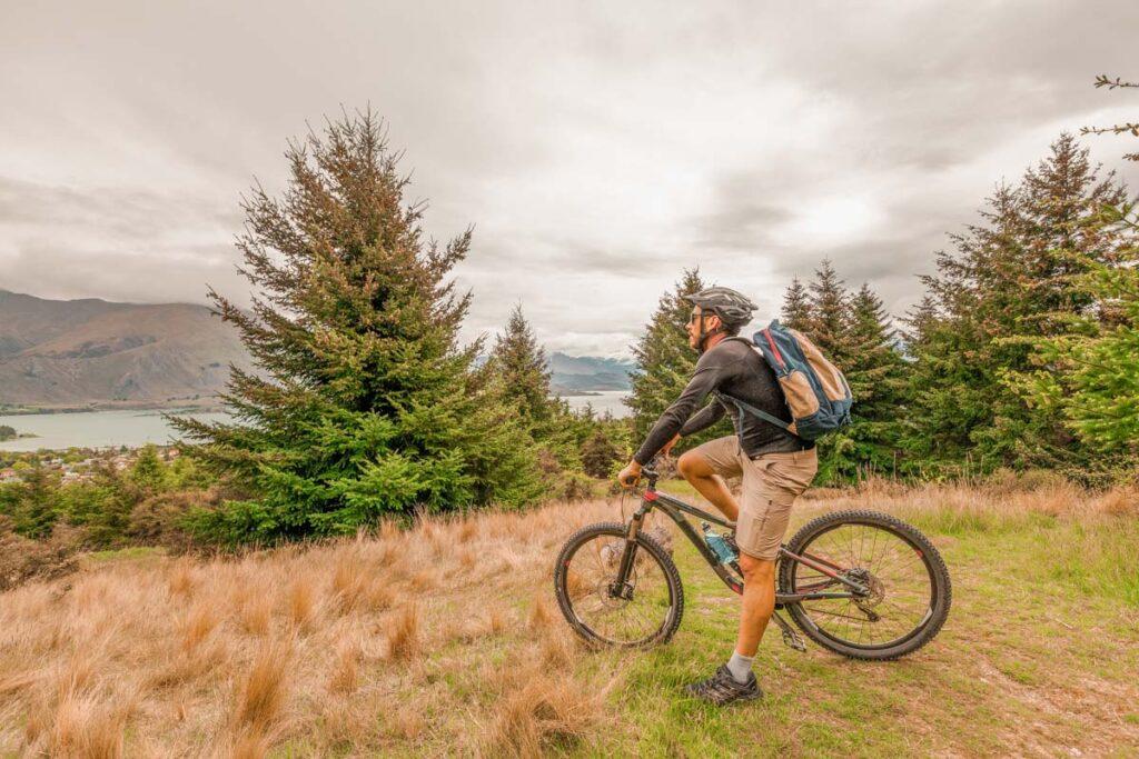 A man sits on his mountain bike overlooking Lake Wanaka