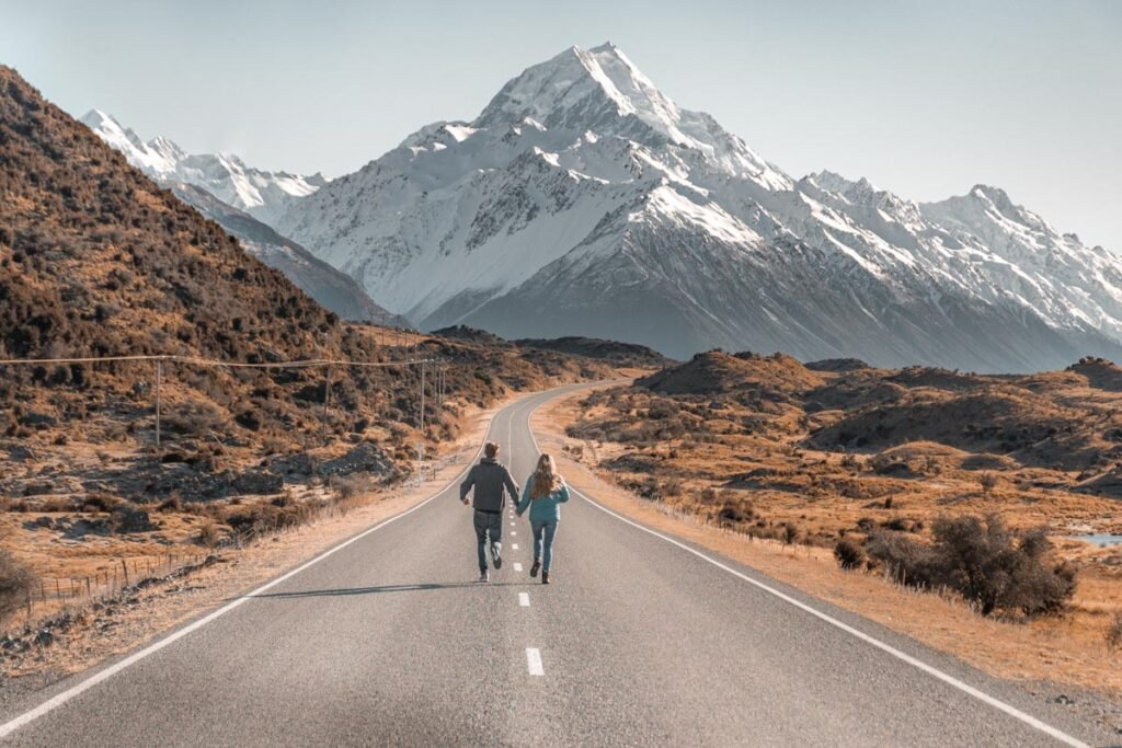 Two people run down the road at the famous Mount Cook Road photo location