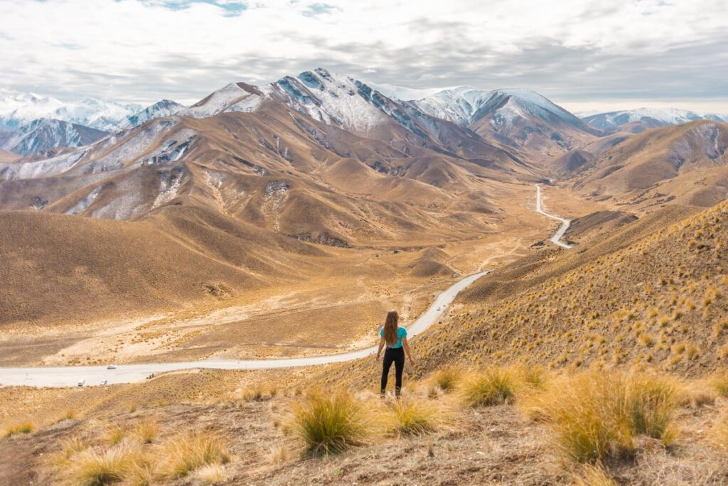 A lady stands at the top of Lindis Pass on a road trip from Queenstown to Mount Cook