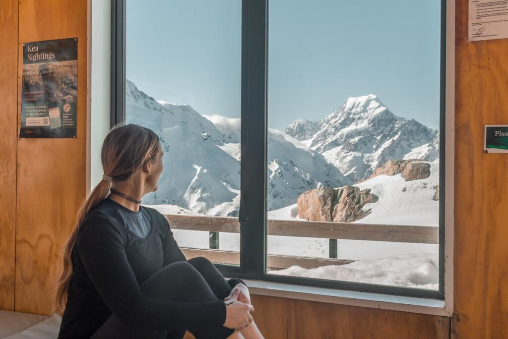 A lady looks out the window of the Mueller Hut at Mount Cook