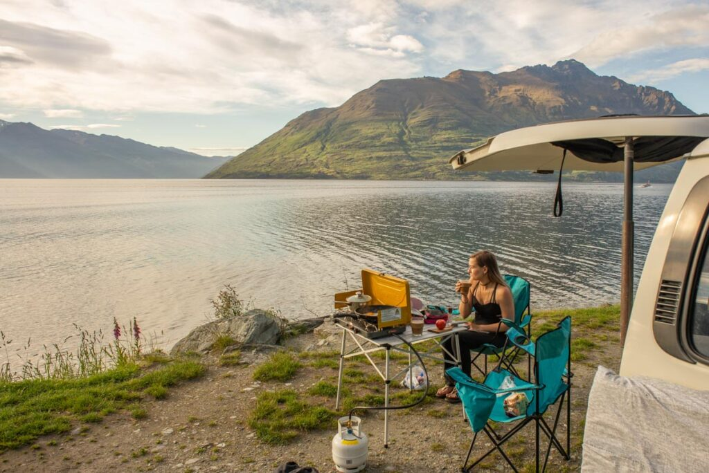 Enjoying vanlife on the shores of Lake Wakatipu with a coffee in hand in Queenstown