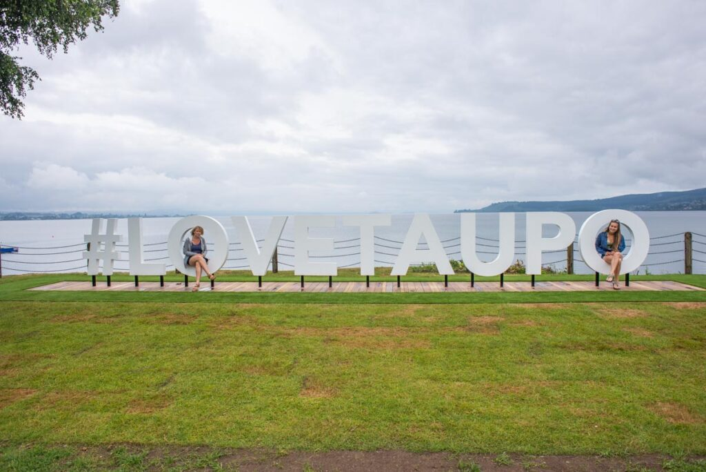 posing for a photo with the I love Taupo sign in Lake Taupo