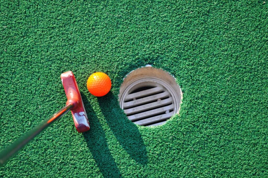 A putter and ball on a mini golf course