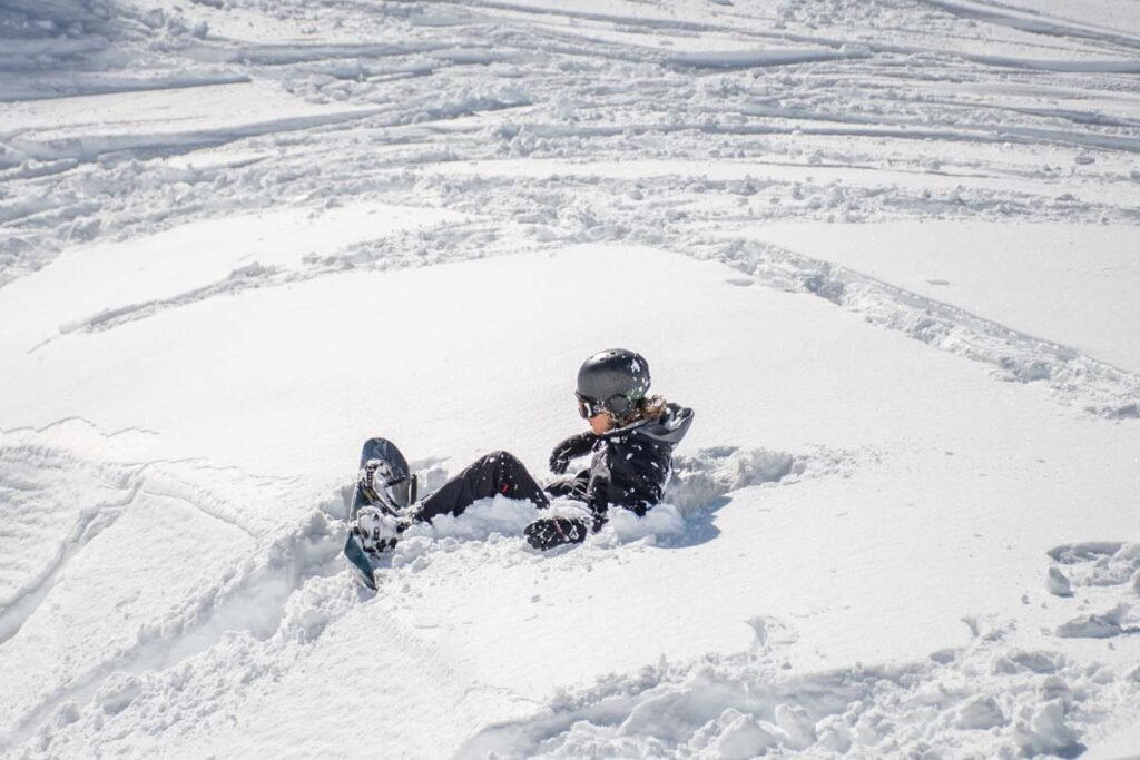 A snowboarder lays in deep powder snow at The Remarkables Ski Resort near Queenstown