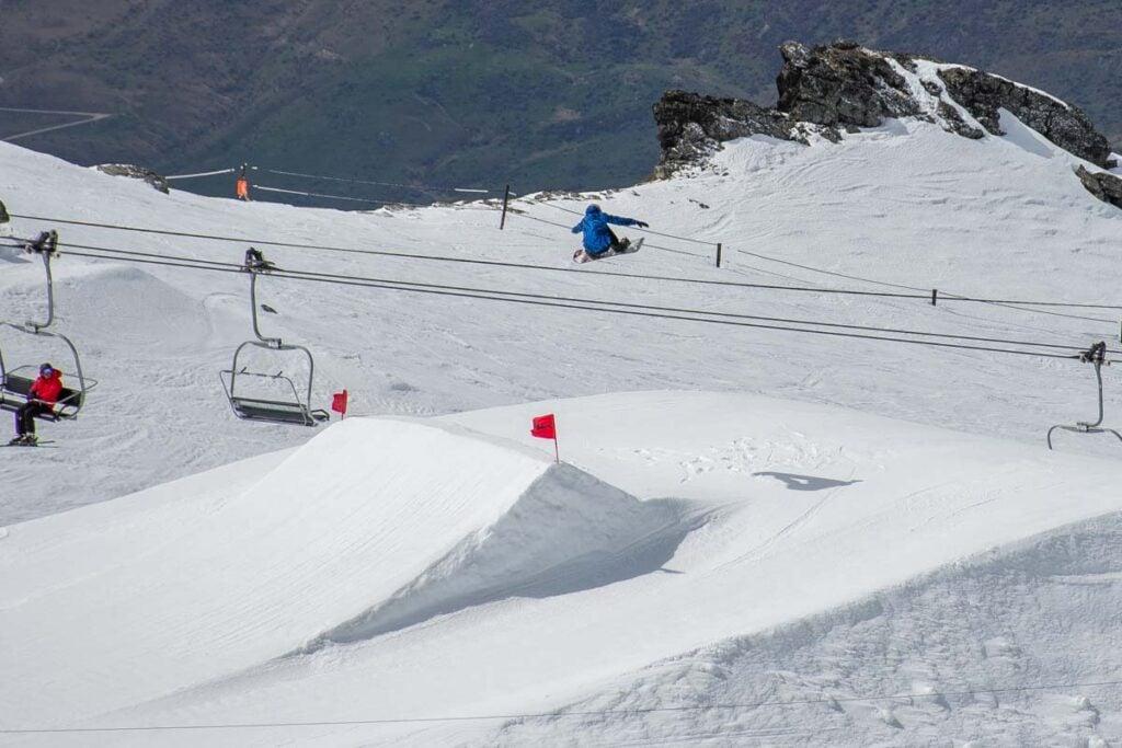 A snowboarder flys over a jump at Cardrona Ski Resort