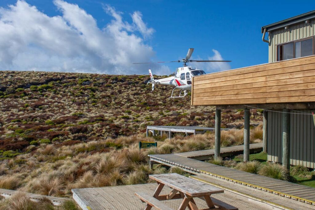 A helicopter lands at the Luxmore Hut