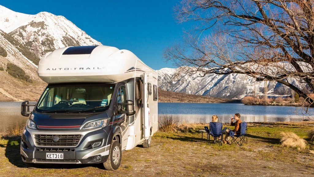 A motorhome by a lake in New Zealand with camp chairs and table out