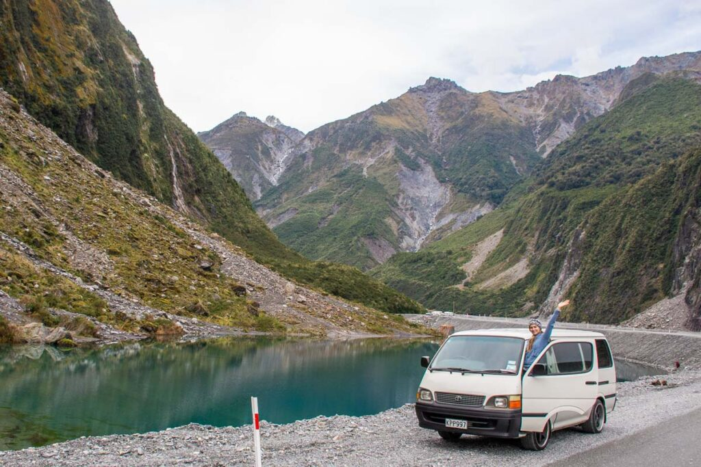 A lady in her campervan at the Fox Glacier parking lot on her way to Franz Josef