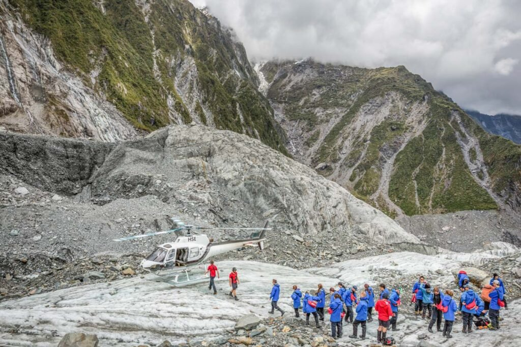 People walk on Franz Josef Glacier after being dropped off by a helicopter